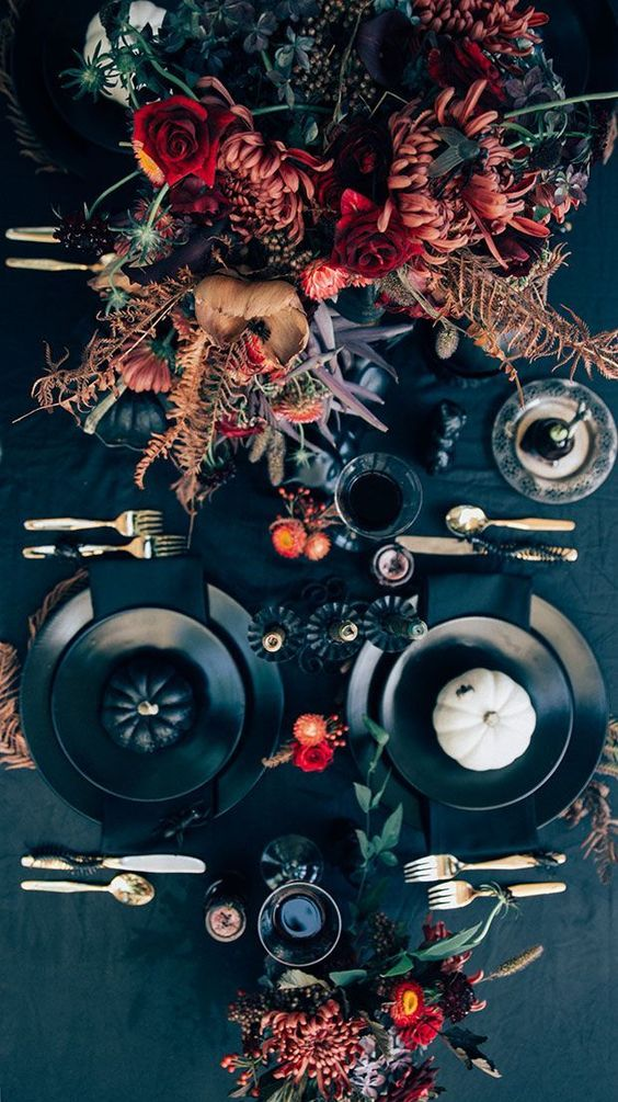 A table setting with black textiles and plates offers the perfect backdrop for bright, bold flower arrangements.