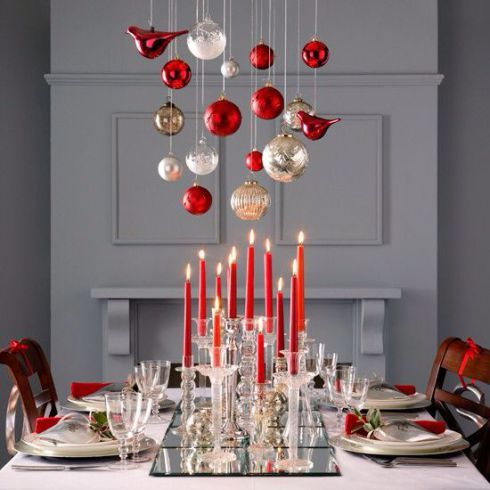 Heighten the visual drama of your table with long, tapered candles and ornaments suspended overhead.
