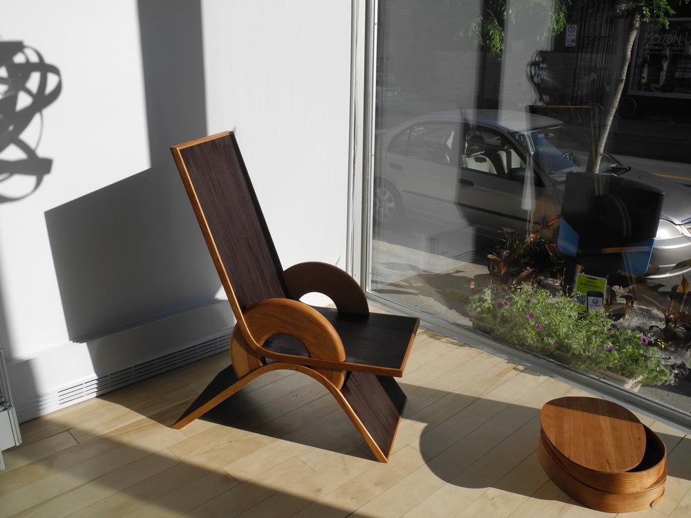 """En vitrine, chaise """"Enfant gâté"""" de Papa Abdy Fall en noyer péruvien et merisier."""