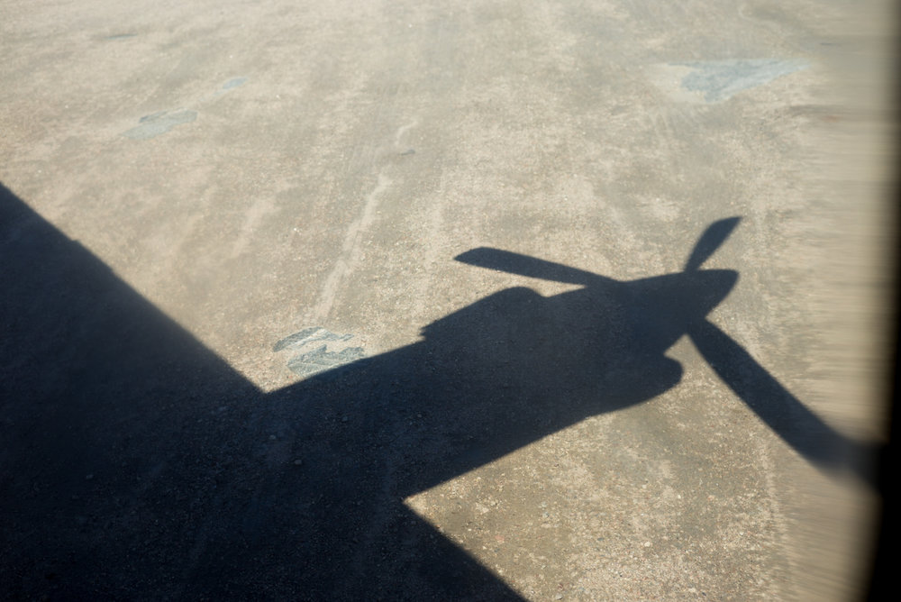 Shadow of the Innu Mikun plane on the gravel runway at William's Harbour, Labrador 2016