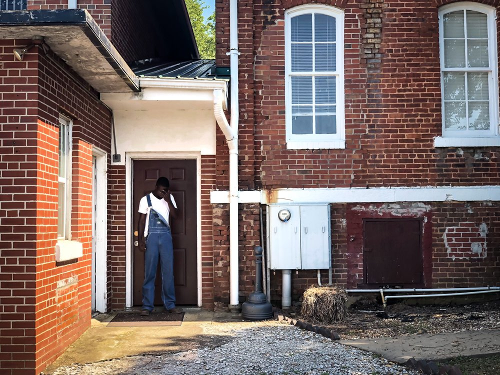 Actor playing Roger Malcom outside the building that was the original jail in Monroe, GA. This jail is the location where Roger Malcom was held and released to Loy Harrison prior to meeting his death at the Moore's Ford Bridge.