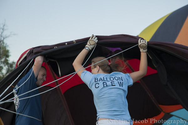 Crew members hold open the balloon so that air can get into the material.