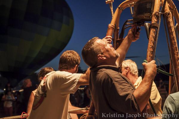 A hot air balloon pilot blows heat into the balloon.