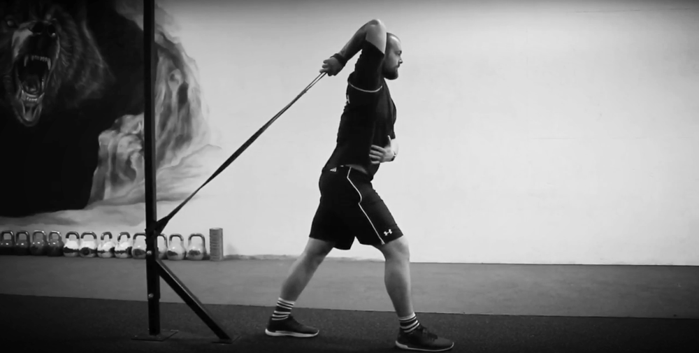 An example of a band being used to mobilise the shoulder joint by pulling the elbow backwards when overhead.