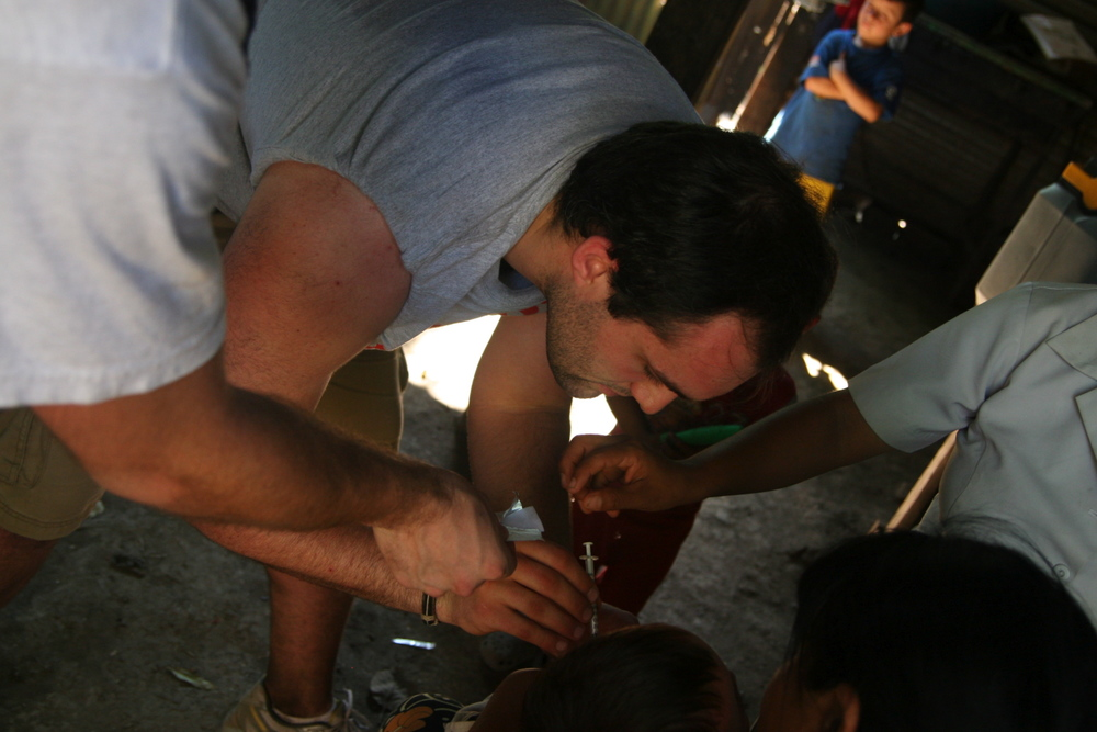 Alex giving a vaccination to a baby.