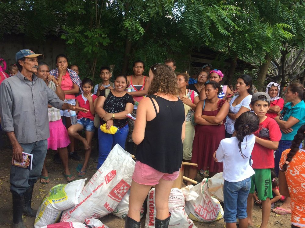 FIMRC Field Operations Manager, Jessica Southern meets with the community of La Uva. They are receiving supplies after walking down the hills for 2 hours.
