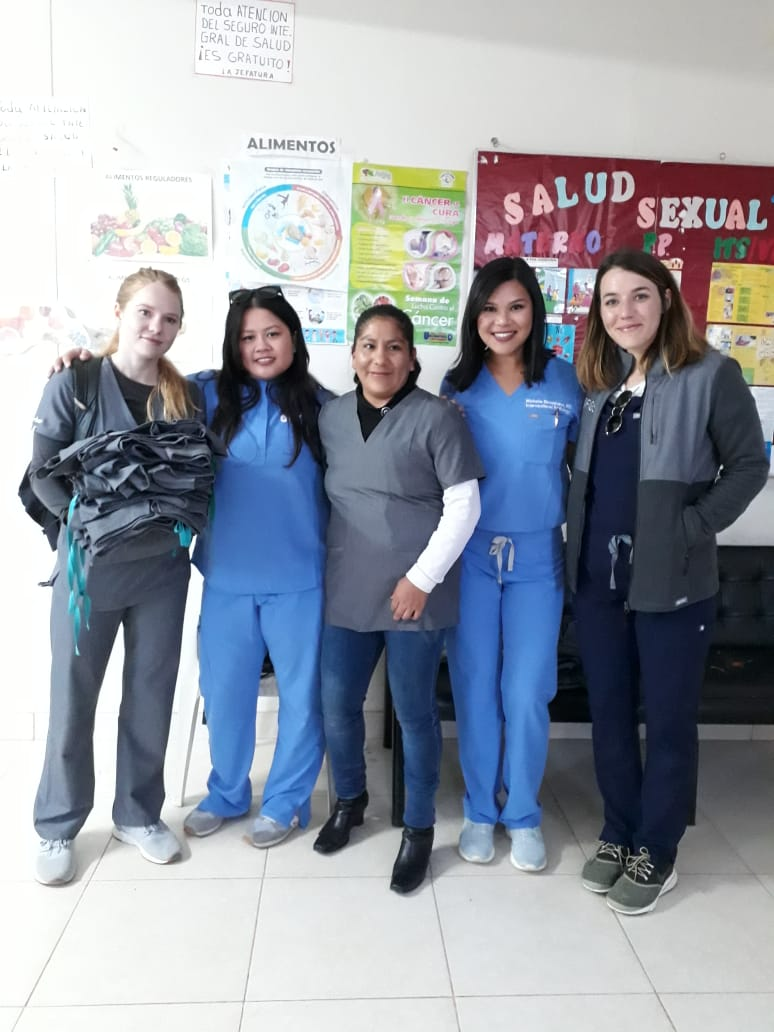 Licencia Consuelo (center), The Chief of  THe Cocharcas Health Post, near Huancayo Peru, looking stylish, in her new FIGS Scrubs, and getting a donation to give out to her team from the FIGS team! (Pictured R to L Jenny, Michelle ( @mmaneevese ), Consuelo, Aileen, Mary