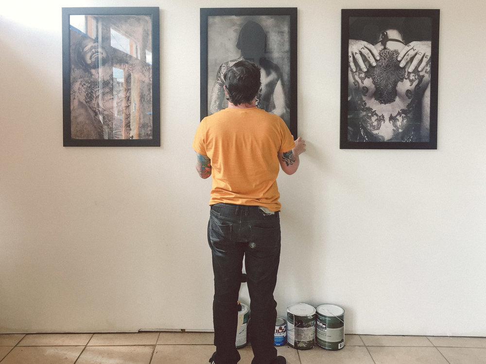 Adam Montegut of the New Orleans Tattoo Museum hanging prints from the Black Ink photo series.
