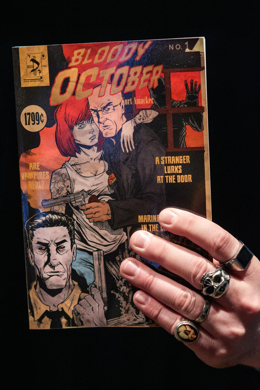 Kurt Amacker holds a copy of his latest novel, Bloody October.