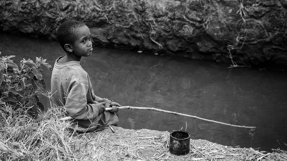 A young boy fishing in one of the canals that supplies water to the rice fields