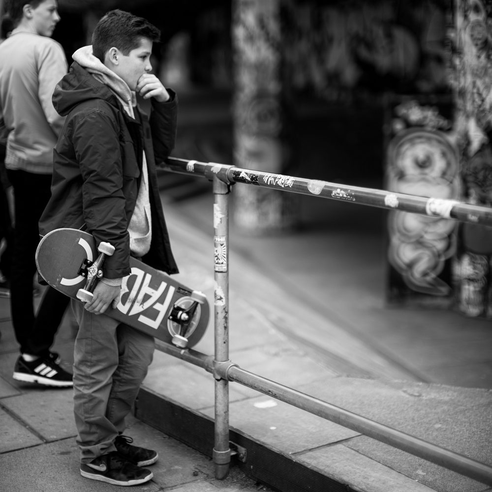 A young skater watches others in the park