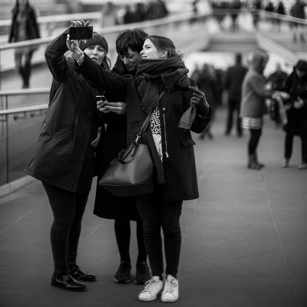 Some tourists pose for a group selfie along the London waterfront