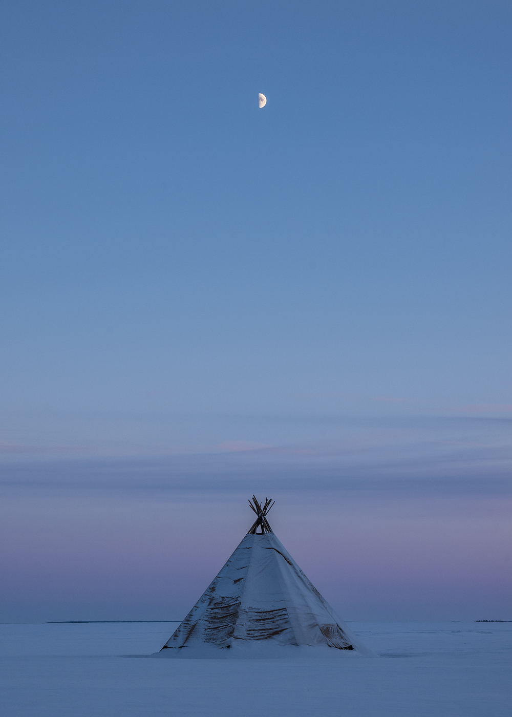 Moonrise over a tent on the frozen archipelago of Swedish Lapland.