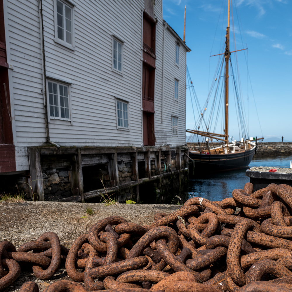 Some rusted chain lays abandoned in a dockyard along the canals of Alesund, Norway
