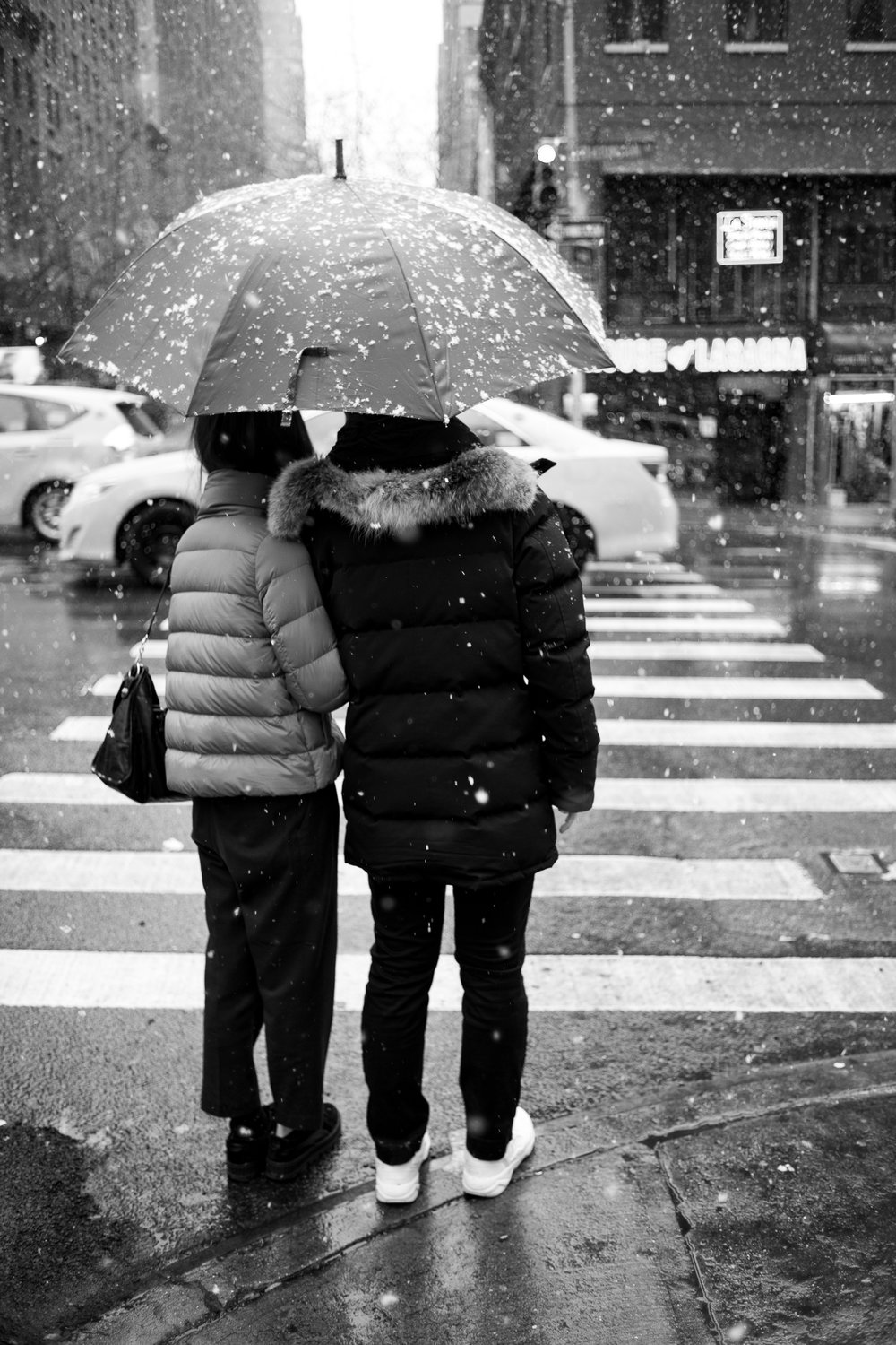 A couple seeks refuge underneath an umbrella during the snowfall