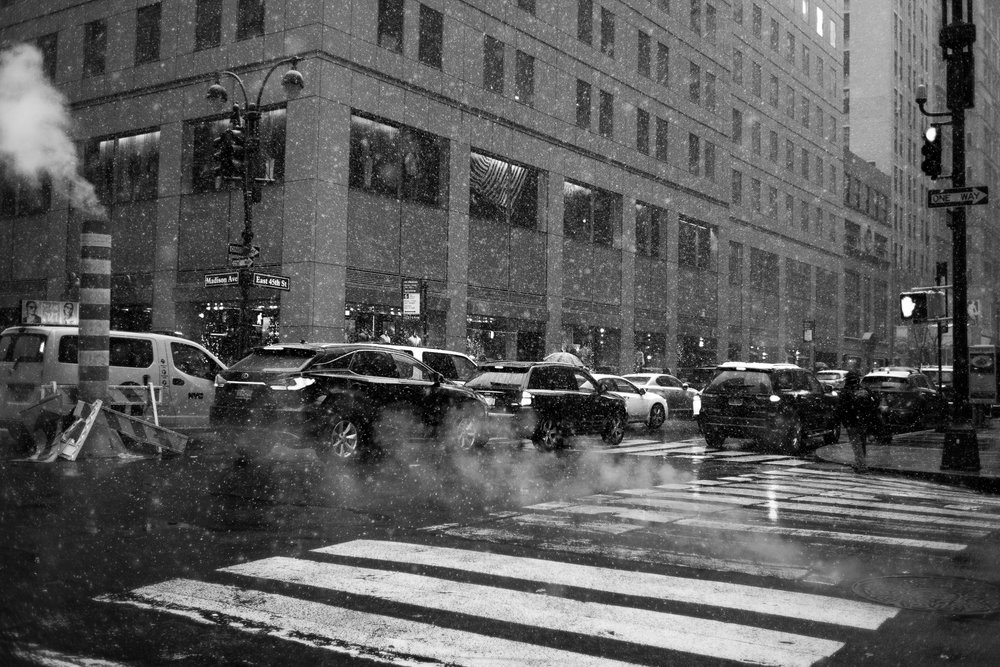 Steam rising from street vents adds to the dramatic effect of the snowfall on this New York street