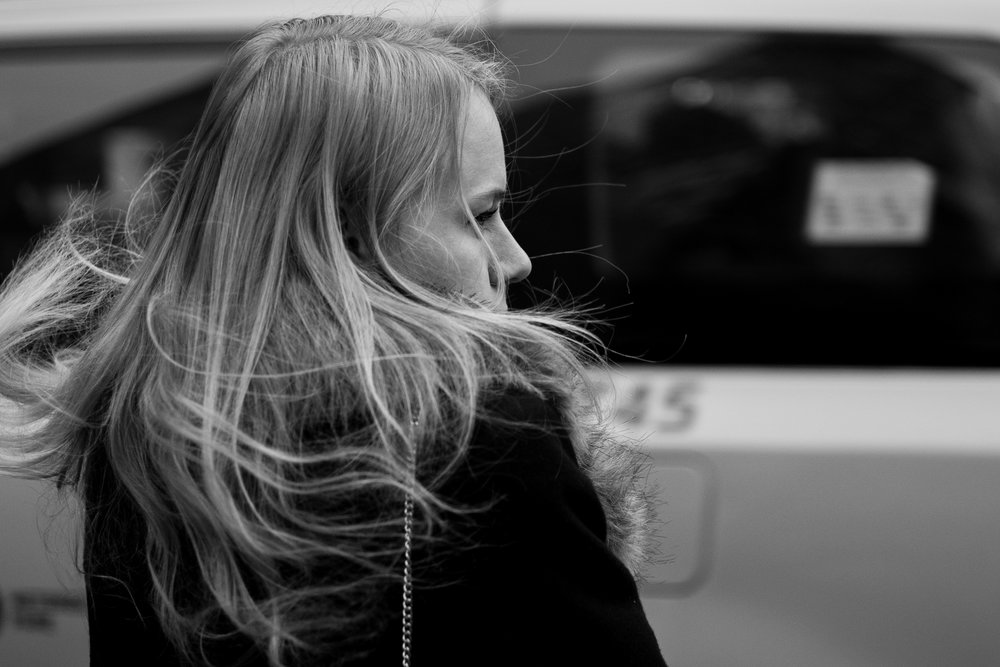 Street Blown.  A woman's hair blows around in the wind caused by cars rushing past on the street nearby.  Leica M10 with 50mm Summicron f/2.