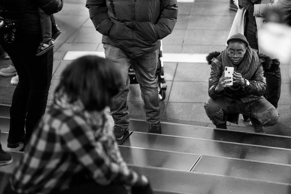 Steps of Time.  Two friends take pictures on the staircase in Times Square. I loved the attire and face of the individual holding the cell phone, so focused the attention of the viewer that direction by having the rest of the image slightly out of focus.  Leica M10 with 90mm Summicron f/2.
