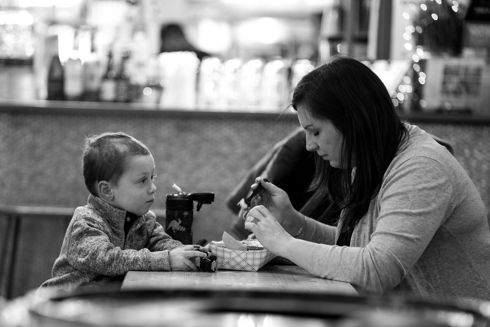 Sharing a Snack.  A mom and son enjoy a Sunday morning snack at an indoor food hall in New York. The scene is very busy with elements that could distract from the story of the shared meal, but selective focus and bokeh help me isolate them and tell the story the way I want.  Leica M10 with 90mm Summicron f/2.
