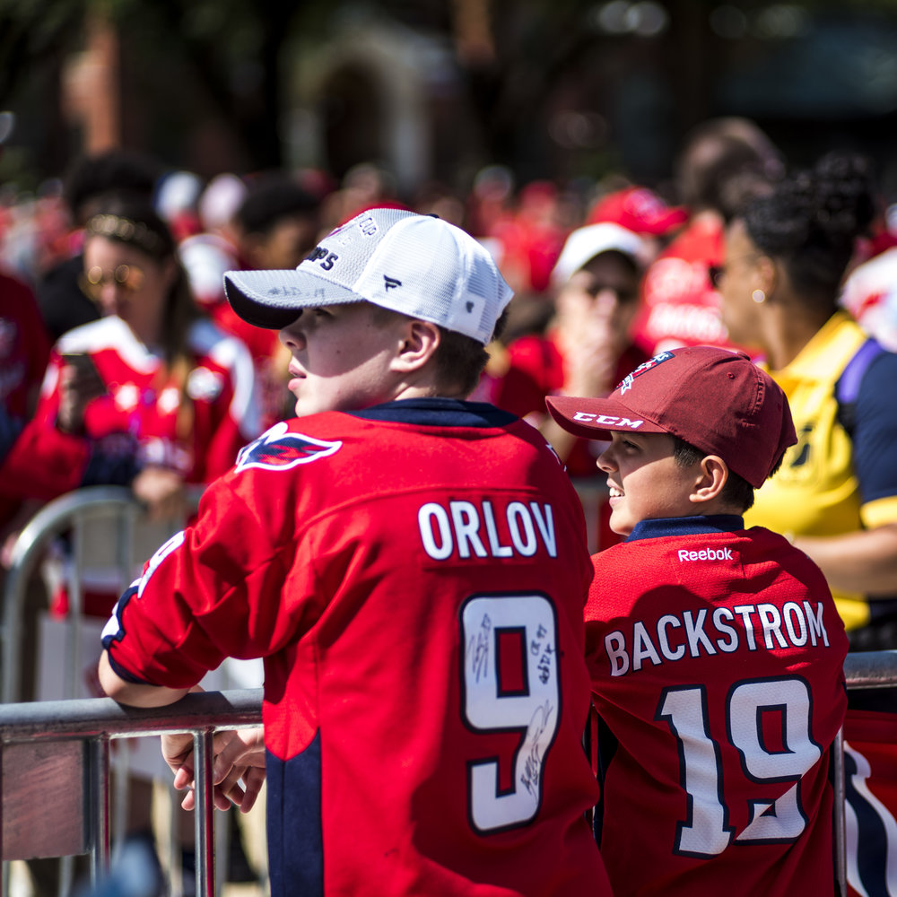 Two young boys lean along barricades, hoping for a glimpse of the Stanley Cup