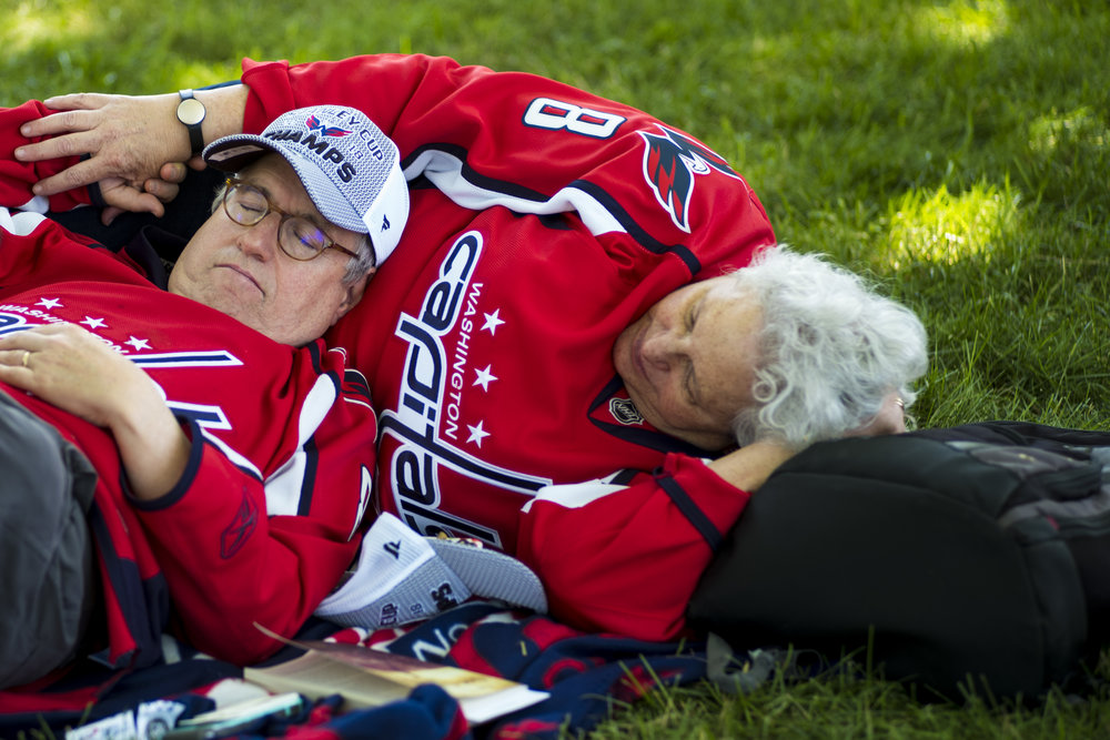 A couple naps in the shade as they wait for the start of the parade