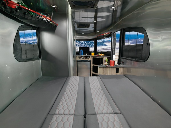"""The """"standard"""" bed in the Basecamp. Normally you arrange the cushions from the bench seating to form a large bed area, but most Basecamp owners want to supplement that with some extra padding. (Photo from Airstream.com)"""