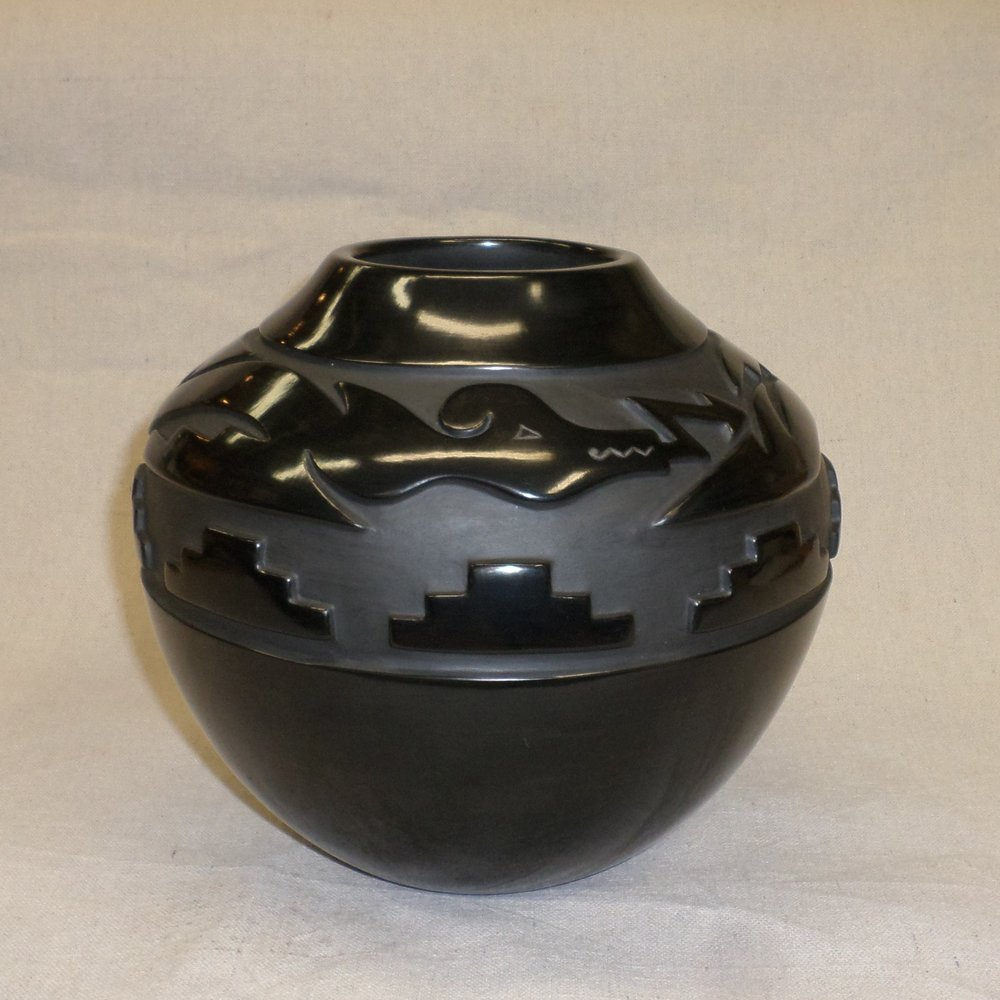 "Black deep carvedtraditional storage jar with Avanyu and Kiva step designs  8-1/"" H x 9-1`/8"" Dia.  SOLD"