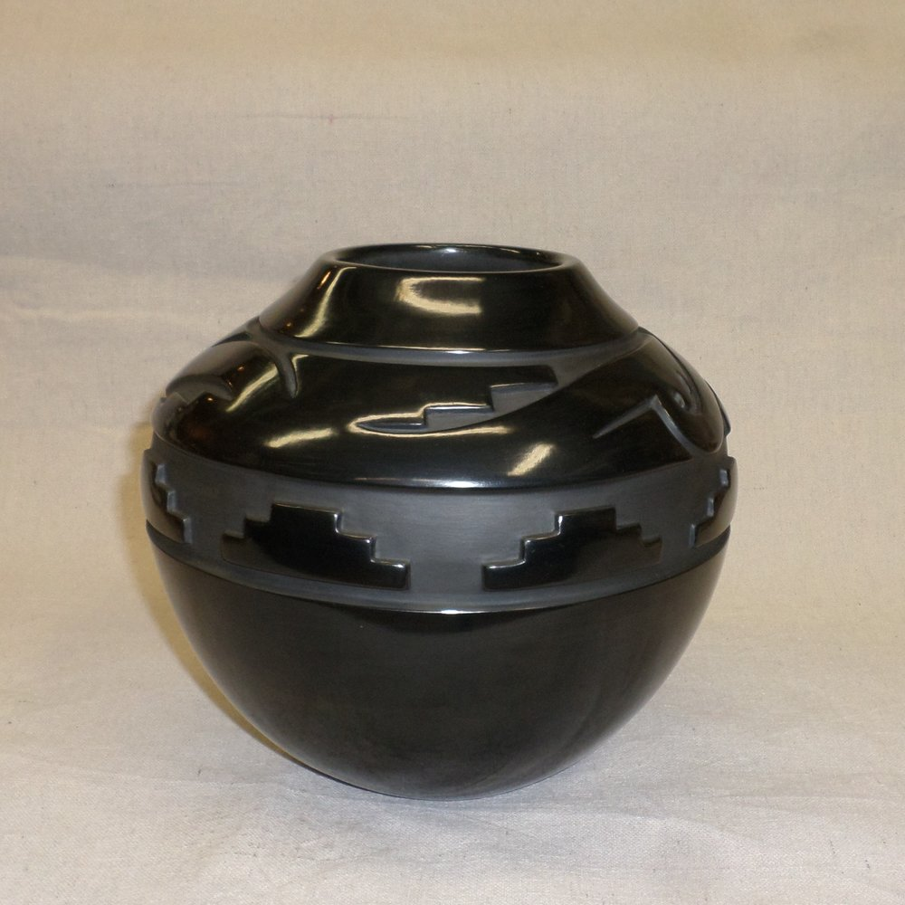 "Black deep carvedtraditional storage jar with Avanyu and Kiva step designs  8-1/"" H x 9-1`/8"" Dia.  Price:  $5,300."