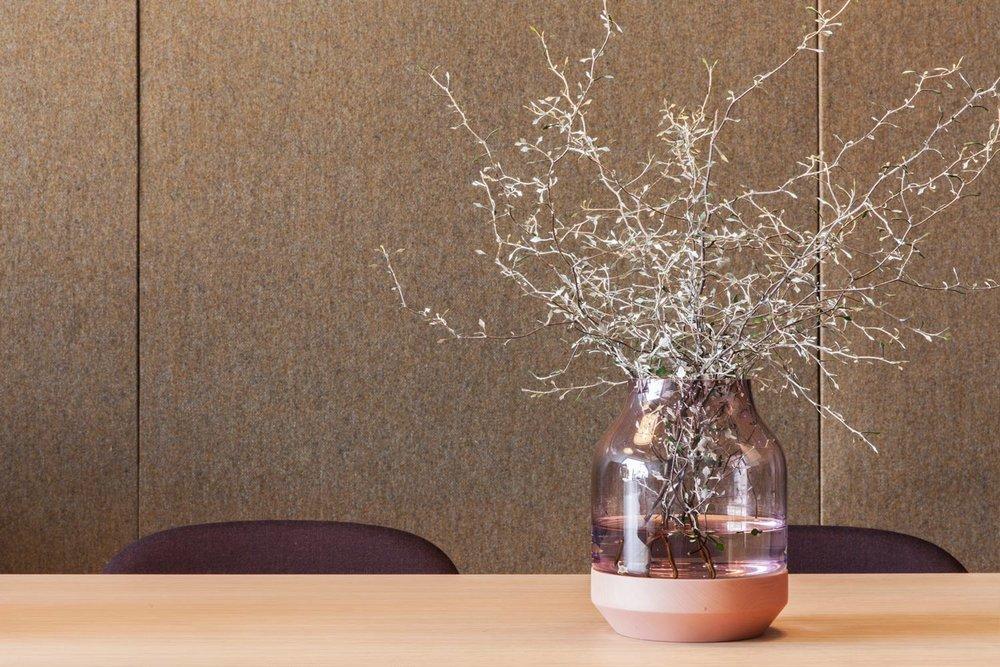 De lyddempende elementene  BasicWall , trukket i tekstilen Amdal fra Gudbrandsdalen uldvarefabrikk, danner et nydelig bakteppe for møtebordet og de plommefargede stolene fra Muuto. Vasen  Elevated Vase setter prikken over I-en.