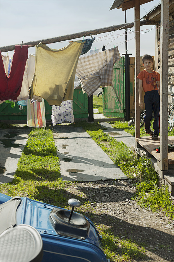 A boy standing outside of his home in Krasnouralsk.