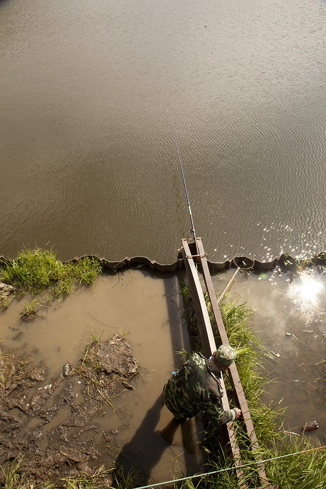 A man sets up his fishing pole under a bridge in town.