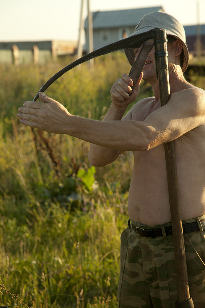 A man sharpens his sickle in the field outside of his home on a summer night. He lives off his land in Kamskie-Polyani, growing and preserving everything he needs for survival. In addition to his garden, he keeps bees and uses the honey to trade for rabbit meat or other goods with his neighbors.