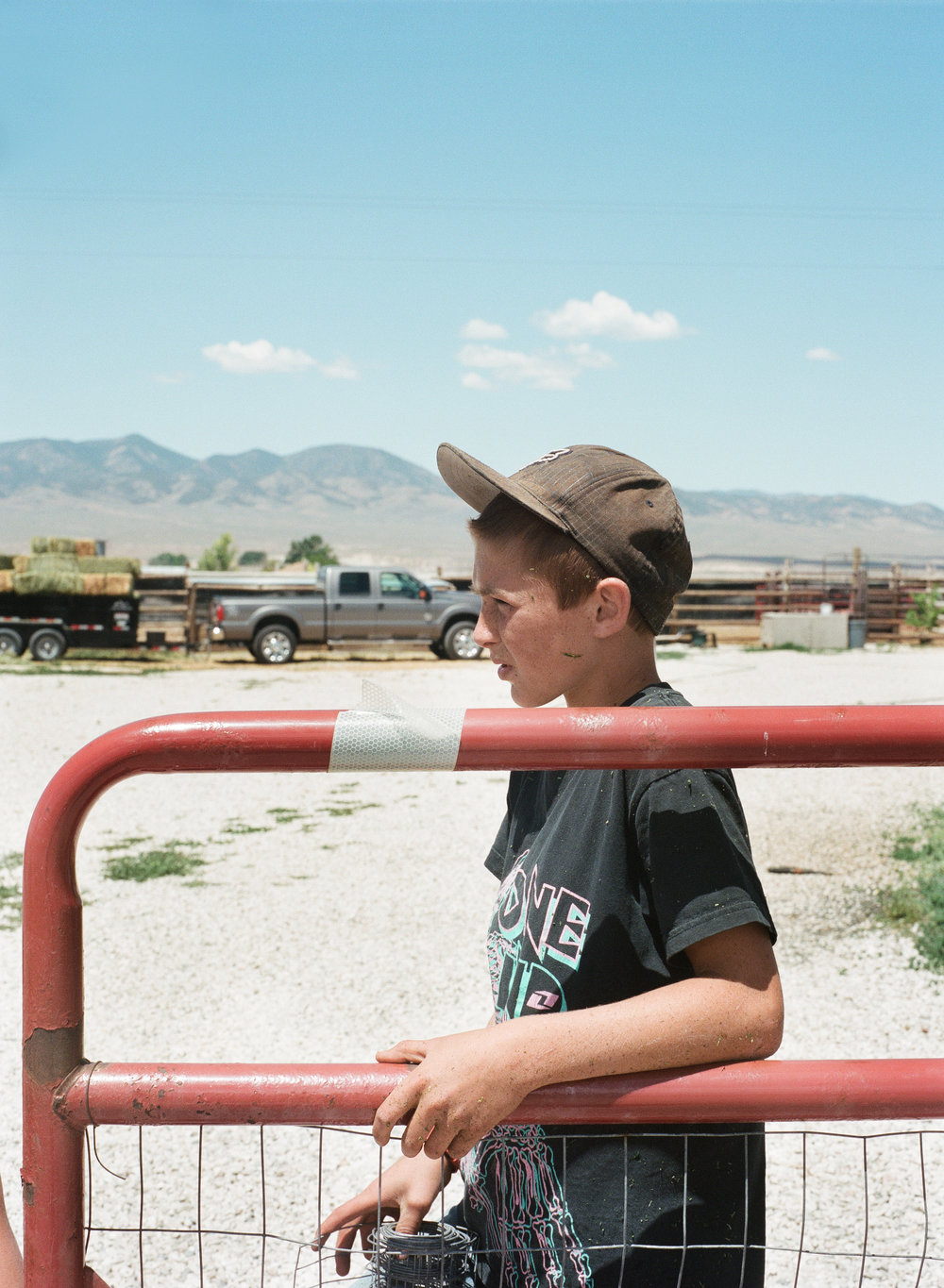 Dylan helping his mother fix the fence. His mother has lived all over the world, but thinks there is nothing better than completing the farm chores every day. Axtell, population 237.  Fall 2014.
