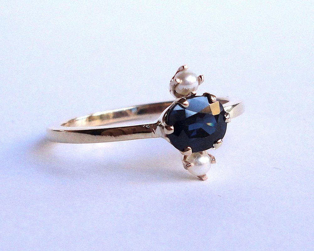 $890  Natural Sapphire and Pearl RING centering on a 0.70 ct oval cut sapphire, accented with two seed pearls 14K yellow gold