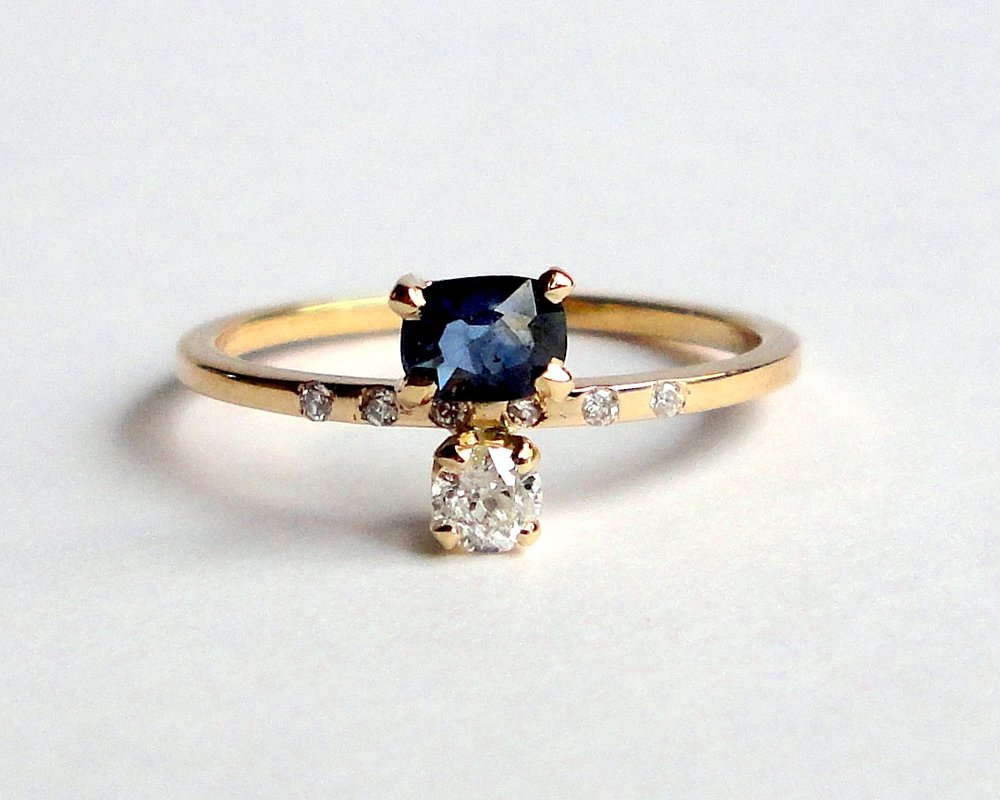 $990  Natural Sapphire and Old Mine Cut Diamond RING set with one cushion cut sapphire and one old mine cut diamond, accented by a line of five diamonds 14K yellow gold