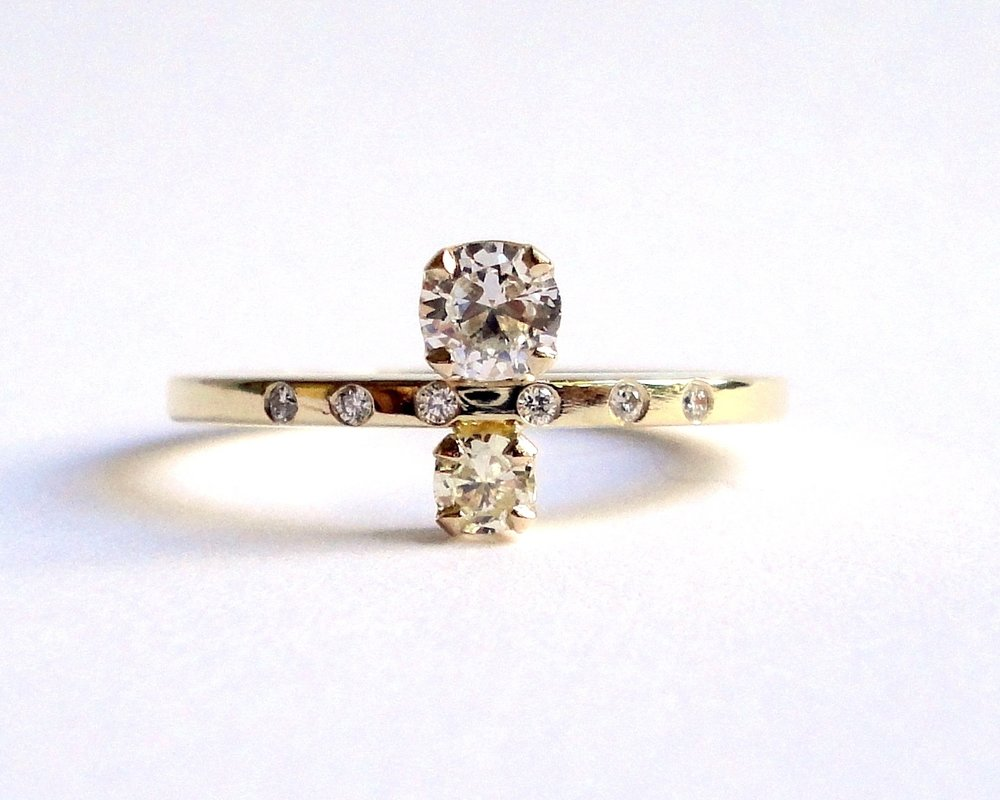 $1510  Diamond and Yellow Diamond RING  set with a round brilliant cut diamond and a yellow diamond, accented by a line of five diamonds  14K yellow gold