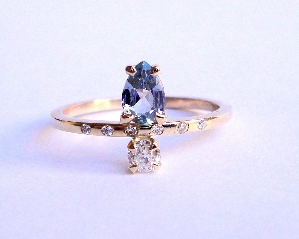 $1150  Natural Sapphire and Old Mine Cut Diamond RING set with one pear shaped sapphire and one old mine cut diamond, accented by a line of five diamonds 14K yellow gold