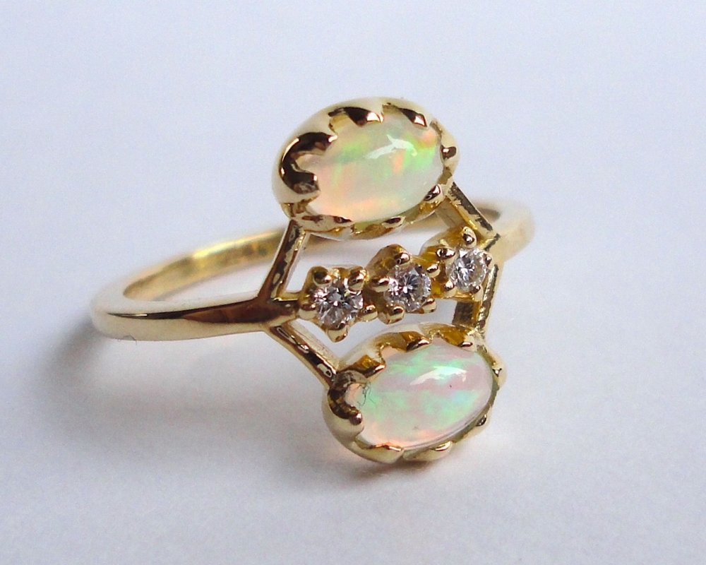 $1220   Opal and Diamond Twin RING  set with two ethiopian opal cabochons accented with a line of diamonds  14K yellow gold