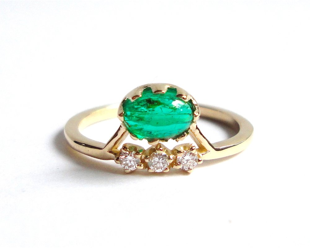 $1320  Emerald Cabochon and Diamond RING  features a vibrant 0.56 ct emerald cabochon prong set and accented with a line of diamonds  14K yellow gold