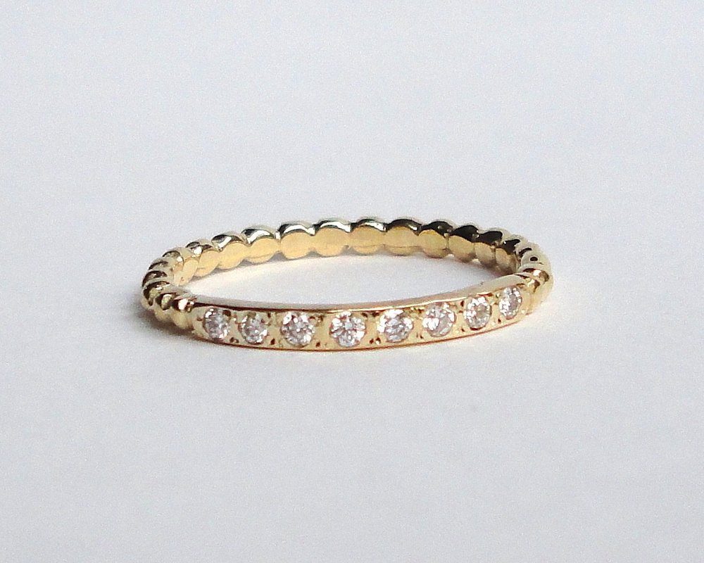 $860  Eight Stone Diamond RING  flat polished gold band, bead set with eight diamonds, finished with a ball patterned band  14K yellow gold