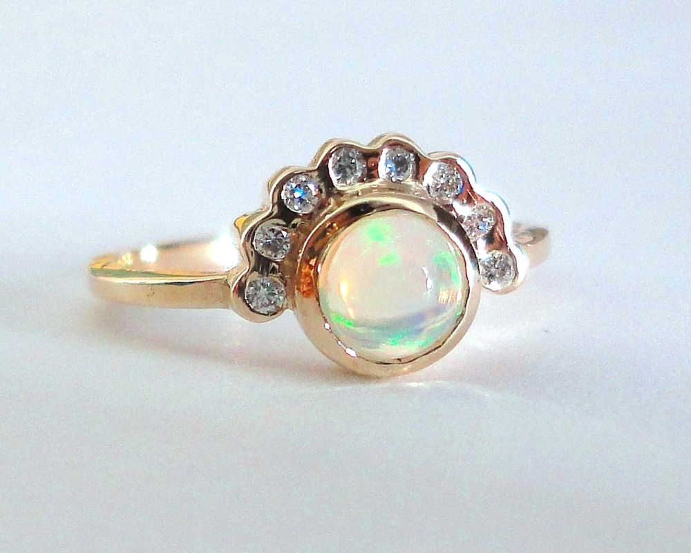 $1180 Opal and Diamond RING centering on a 5.2mm ethiopian opal, beautifully bezel set with a half moon diamond crown 14K yellow gold