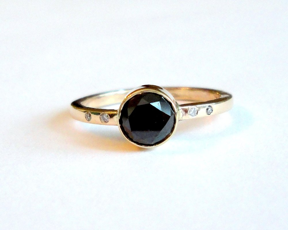 $1640 Black Diamond RING centering on a stunning 1.01 ct round brilliant cut black diamond, bezel set and finished with a handmade recycled gold band accented by four diamonds 14K yellow gold