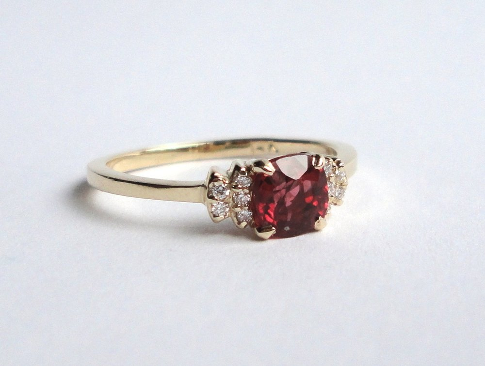 $1150   Red Spinel Diamond Bow RING  centering on a beautiful 0.50 ct vibrant red spinel, accented with diamond set bow shoulders   14K yellow gold