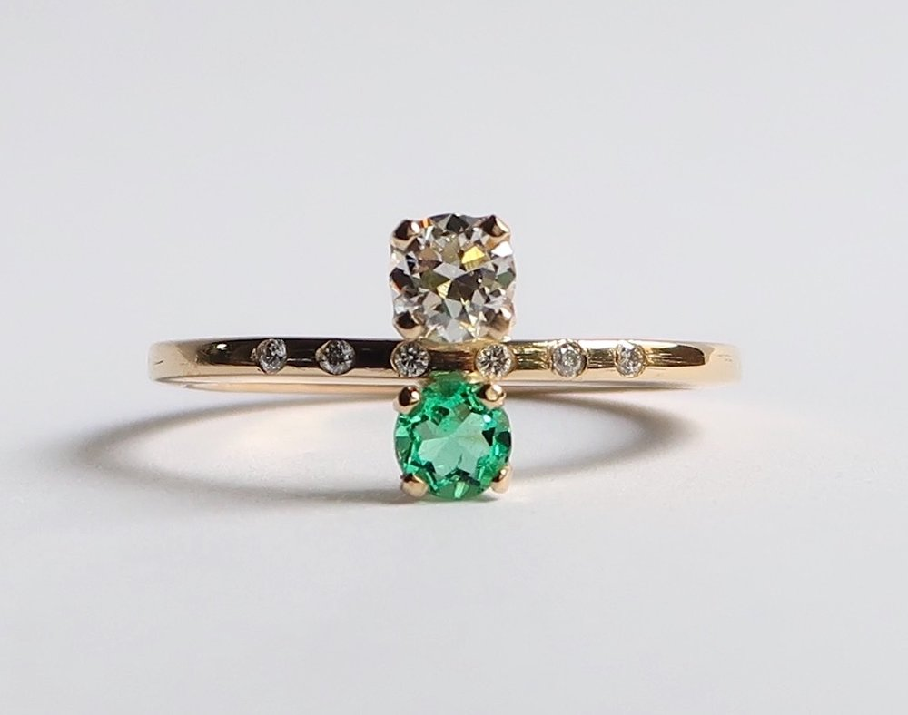 $1450  Old European Cut Diamond and Emerald RING  set with one old european cut diamond and an emerald, accented by a line of five diamonds  14K yellow gold