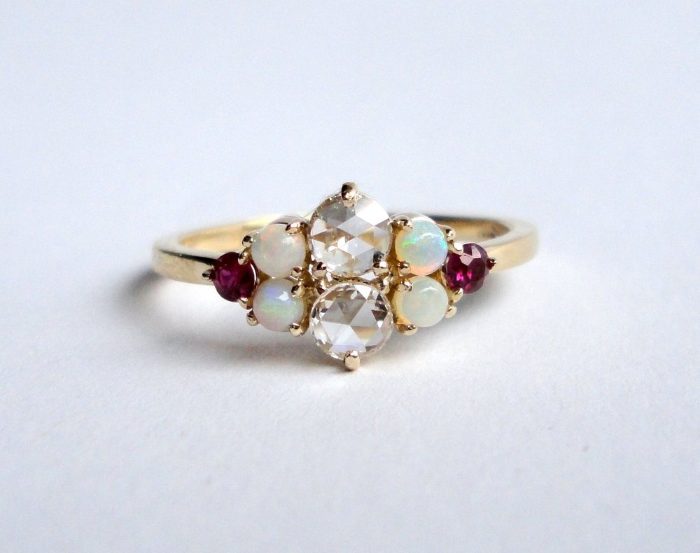 $1350  Rose Cut Diamond, Opal and Ruby RING  centering on two rose cut diamonds, framed by opal and ruby cabochons  14K yellow gold