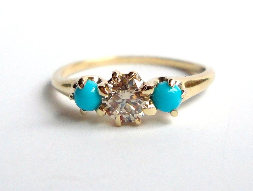 $1390  Diamond and Turquoise RING  centering on a 0.36 ct fancy yellowish brown diamond, flanked by two turquoise cabochons on each side  14K yellow gold