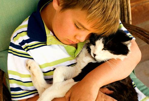 getty_rf_photo_of_boy_affectionately_hugging_cat.jpg
