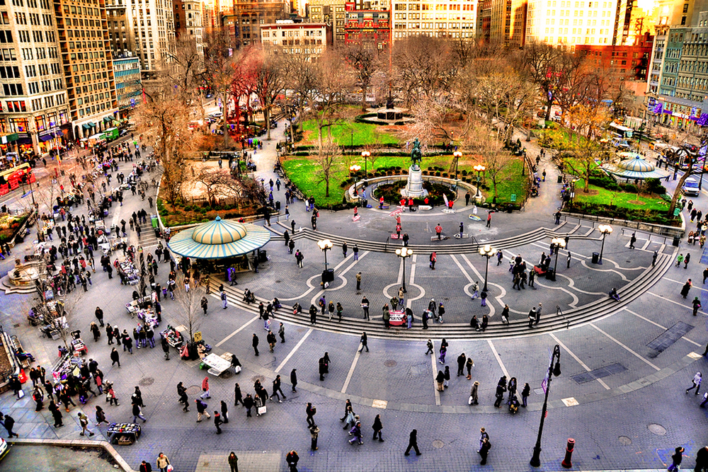Image of Union Square from adjacent building showing the main plaza, park, and surrounding buildings. Union Square offers an immense diversity of conditions and actors with an array of activity from major transit hub and farmer's market to a history of public protests and high concentration of both informal and formal transactions. Source: David Robert Bliwas, creative commons
