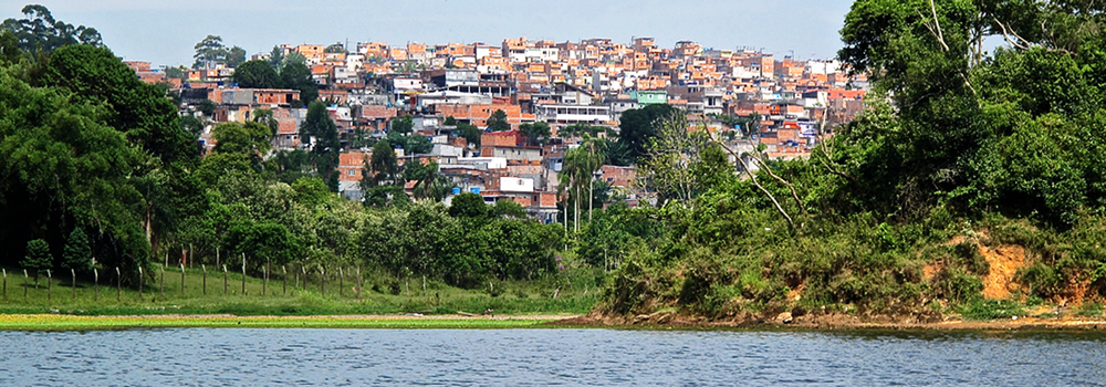 Image of the Guarapiranga reservoir from a boat, with a view of the water's edge and a favela in the background.  Guarapiranga has a mix of neighborhood types with a wide range of income levels.  Source:  Sara Minard