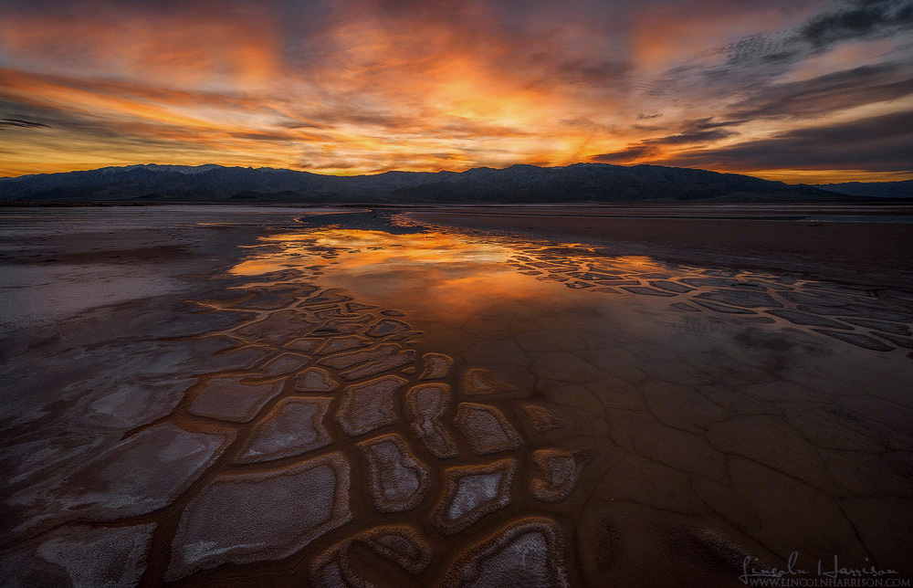 Fiery sunset over emerging polygons at salt creek in death valley